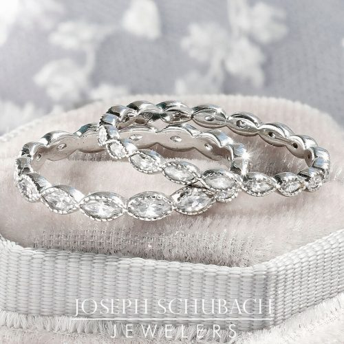 A bezel set marquise diamond wedding band with milgraine.
