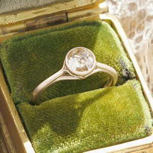 A Schubach Exclusive! Custom made bezel set Scroll solitaire engagement ring with a champagne color, rose cut center diamond and surprise diamond accent.